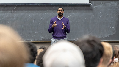Colston speaking to a large group of people